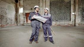 Twee mensen gekleed in eenvormige en veiligheidsbouwvakkers bevinden zich op bouwterrein en kijken over werkplaats De voorman is stock videobeelden