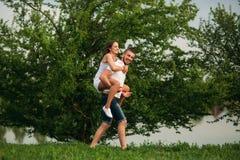 Twee mensen hebben pret Meisje en jongen rond dichtbij het meer in werking dat wordt gesteld dat stock afbeeldingen