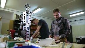 Twee mensen herstellen de robot in de workshop stock videobeelden