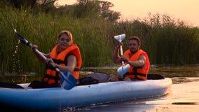 Twee mensen in het roeien van roeispanen die in een kajak op het meer in de zonsondergang zitten Langzame Motie stock video