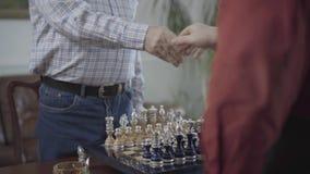Twee mensen het schudden overhandigt een schaakraad vóór beginspel en zit bij de kleine lijst Het mooie die schaak wordt geplaats stock footage