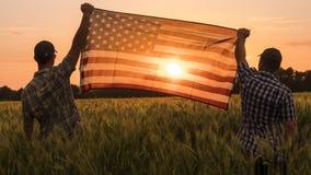 Twee mensen hieven energiek de vlag van de V.S. op een schilderachtig gebied van tarwe op stock foto's
