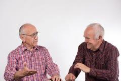 Twee mensen in kleurrijke overhemden hebben bespreking stock afbeelding