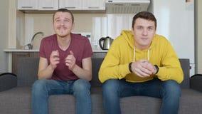 Twee mensen letten op een voetbalwedstrijd op TV en genieten van de overwinning van hun favoriet team stock video
