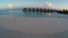 Twee mensen in liefde tijdens zonsondergang op het tropische strand - antenne stock video