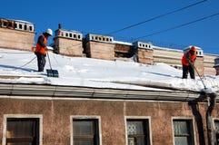 Twee mensen met schoppen verwijderen sneeuw uit een dak Stock Afbeelding