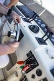 Twee mensen op een boot, met handen en wapens die - één mens drijft en werkt bij cockpit tonen en andere ontspant en let op - u stock fotografie