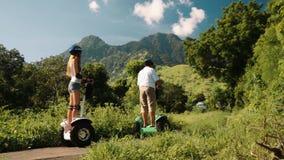 Twee mensen op segway in heuvels, de Balinese mens en Kaukasische vrouw stock video
