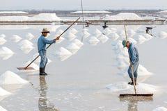 Twee mensen organiseren zout binnen in stapels bij de zoute gebieden van Hon Khoi Stock Foto's