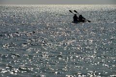 Twee mensen paddelen een kajak op het overzees stock foto's