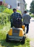 Twee mensen snijden gras Stock Afbeeldingen