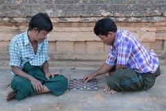 Twee mensen spelen met kleine stenen Stock Afbeeldingen