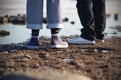 Twee mensen in tennisschoenen zijn op het strand stock afbeelding
