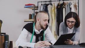 Twee mensen vormen ontwerpers die met schetsen voor het naaien van een nieuwe inzameling op het mooie kantoor met verschillend we stock video