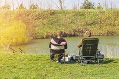 Twee mensen zitten als voorzitter dichtbij de rivier vissend met hengels stock fotografie