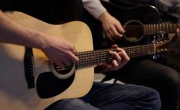 Twee mensenduet die een melodie op gitaren spelen stock foto