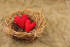 Twee met de hand gemaakte harten in het nest Stock Foto