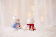 Twee met de hand gemaakte sneeuwmannen met Kerstmis lichte achtergrond Royalty-vrije Stock Foto