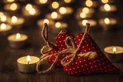 Twee met de hand gemaakte valentijnskaartharten, brandende kaarsen, romantische atmosfeer Twee harten op een houten raad De dag v Stock Foto's