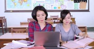 Twee middelbare schoolstudenten die in klaslokaal bestuderen stock videobeelden