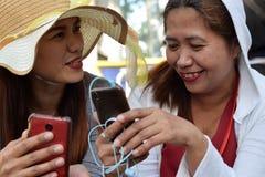 Twee 2 midden oude vrouwen die pret hebben die gedachten en verhalen delen die smartphone houden royalty-vrije stock foto's