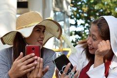 Twee 2 midden oude vrouwen die pret hebben die gedachten en verhalen delen die smartphone houden stock afbeelding