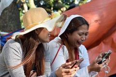 Twee 2 midden oude vrouwen die pret hebben die gedachten en verhalen delen die smartphone houden royalty-vrije stock fotografie