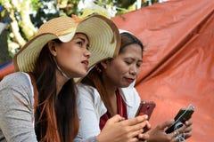 Twee 2 midden oude vrouwen die pret hebben die gedachten en verhalen delen die smartphone houden stock foto's