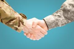 Twee militaire mensen die handen op witte die achtergrond schudden - sluit omhoog studio op lichtblauwe achtergrond wordt geschot royalty-vrije stock foto