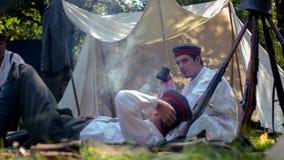 Twee militaire mensen die op een grond rusten stock afbeeldingen