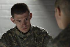 Twee militairen die in donkere horizontale ruimte samenkomen, Stock Foto