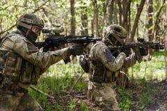 Twee militairen op aanval in bos Stock Foto's