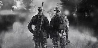 Twee militairen van een speciale eenheid bevinden zich in een rokerig bos royalty-vrije stock fotografie