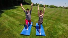 Twee Millennials die Yogaposities buiten uitvoeren stock footage