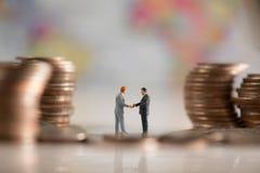 Twee miniatuurzakenlieden maken een overeenkomst Stock Foto's