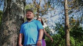 Twee minnaars dichtbij een boom op de rivierbank Mooi kader in aard Het meisje koestert erachter de kerel van stock footage
