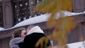 Twee minnaars die en onder een boom in de winter kussen koesteren Zeer mooi en diep kader De minnaars hebben gelukkige en vrolijk stock videobeelden