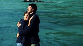 Twee minnaars die op de achtergrond van blauw water koesteren stock videobeelden