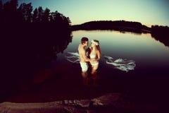 Twee minnaars in een meer bij nacht Meisje en mens bij zonsondergang in LAK Royalty-vrije Stock Afbeelding