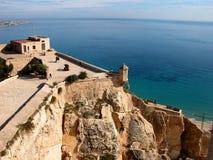 Twee minnaars omhelzen het overzien van het overzees van een kasteel in Spanje royalty-vrije stock fotografie