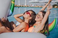 Twee modellen die op vlotter in zwembad koelen Zij dragen zwempakken en zonnebril Eerste model koel en houdt ogen stock afbeeldingen
