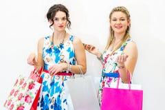 Twee modellen die zich met het winkelen zakken en slimme telefoon bevinden stock fotografie