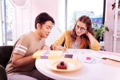 Twee moderne niet-gegradueerden die kaastaart en het bestuderen eten royalty-vrije stock afbeelding