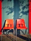Twee moderne oranje plastic stoelen tegen een blauw plooien muur stock fotografie
