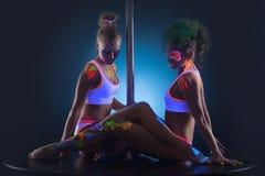 Twee moderne pooldansers met UVmake-up Stock Fotografie