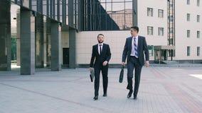 Twee modieuze bedrijfsmensen die slimme kostuums dragen die aan het bureau lopen die over volgende vergadering spreken stock video