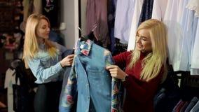 Twee modieuze blondemeisjes kiezen kleren in een grote kledingsopslag stock footage