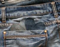 Twee modieuze harten worden gesneden van blauw denim gluurt uit van zijn po Stock Fotografie