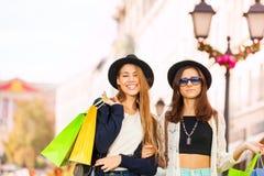 Twee modieuze jonge vrouwen die met het winkelen zakken lopen Stock Foto's