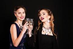 Twee modieuze jonge vrouwen met glazen champagne Royalty-vrije Stock Fotografie